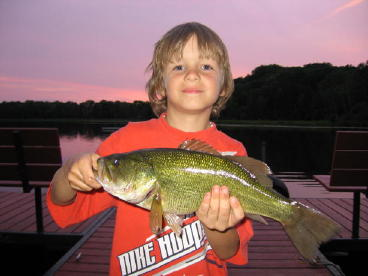 Brenan S. couldn't be prouder of this nice bass he caught and released from our dock, July.