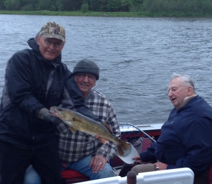 Dave holds a 25 inch walleye that cousin George N caught and released on Benoit Lake.  Uncle John admires the fish.