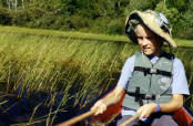 "Jacob uses traditional cedar ""knockers"" to gather wild rice from a local lake."